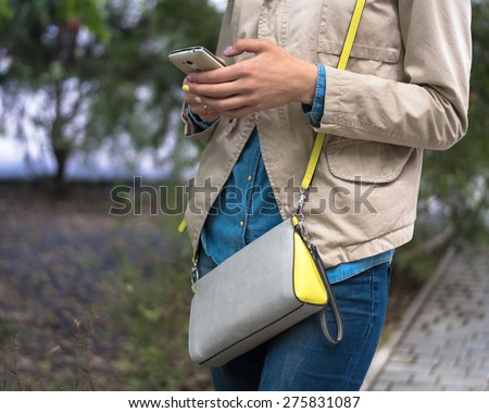 Young girl stands on the sidewalk and typing a message on her white mobile phone. The girl is wearing a beige jacket, denim shirt and jeans. On her shoulder gray yellow handbag.