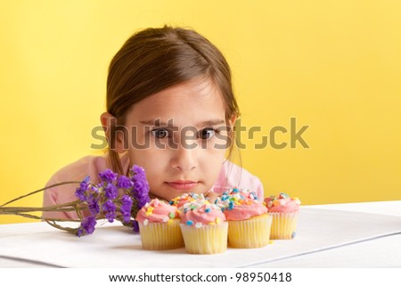Young girl staring at a bunch of cupcakes with big brown eyes on a yellow background - stock photo