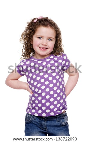 Young girl stood with her hands on her hips smiling at the camera, isolated on a white background