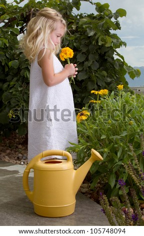 young girl stopping to smell flowers while watering them - stock photo