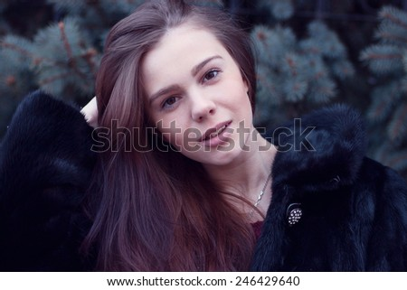 Young girl straightens hair in winter park - stock photo