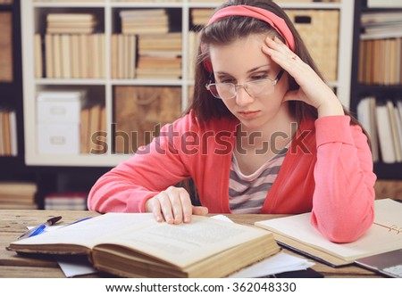 Young girl student sitting in the library and work at the table