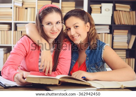 Young girl student sitting in the library and work at the table - stock photo