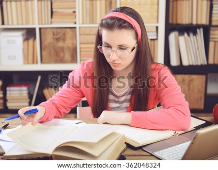 Young girl student sitting in the library and work at the table, the use of a laptop.