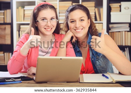 Young girl student sitting in the library and work at the table, the use of a laptop - stock photo
