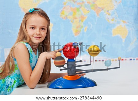 Young girl study solar system in geography science class using a scale model - stock photo