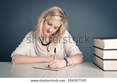Young girl studying against dark background.