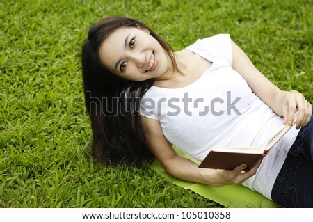 Young girl studying outdoors lying on grass - stock photo