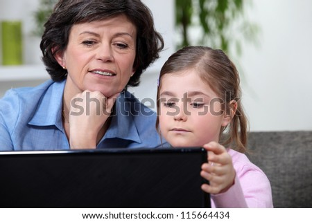 Young girl surfing the Internet with her grandmother - stock photo