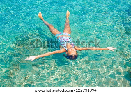 Young girl swimming in the transparent sea - stock photo