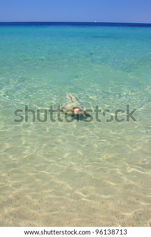 Young girl swimming under water in the sea