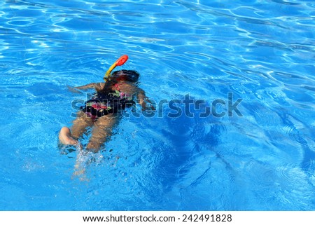 Young girl swimming with diving mask in the pool - stock photo