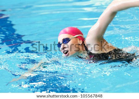 young girl swims freestyle in the pool - stock photo