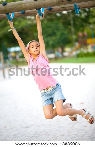 Young girl swinging on monkey bar at outdoor playground - stock photo