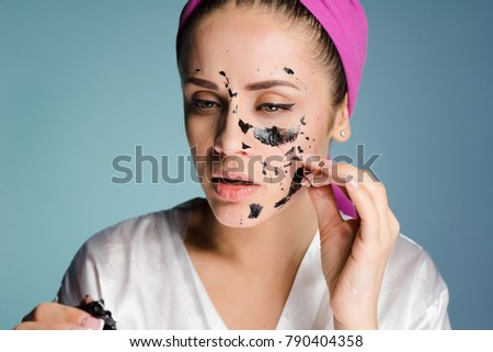 young girl takes off her black mask on a blue background