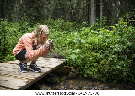Young girl taking a photo outdoors in a forest