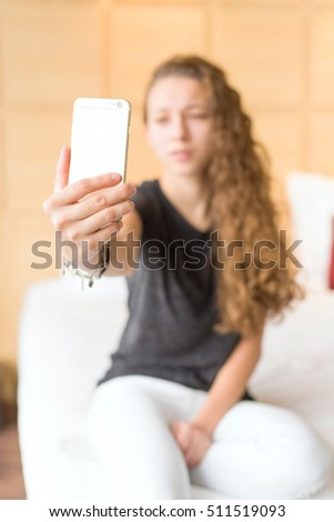 young girl taking a picture with your mobile phone in your room