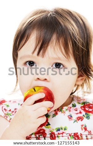 Young girl taking bite from big red apple