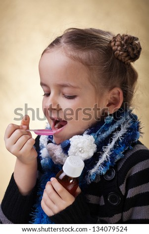 Young girl taking cough medicine syrup - stock photo