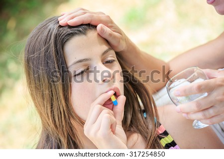 young girl taking medicine in pill with water glass - stock photo