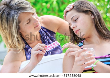 young girl taking one tablet of her mother's hand - stock photo