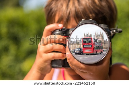 Young girl taking photos of London Bus by professional digital camera. - stock photo