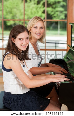 Young girl taking piano lessons from a music teacher