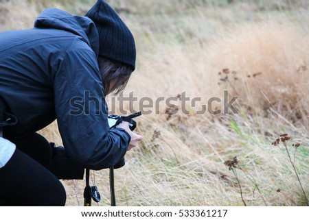 Young girl taking pictures with a camera in the brown field