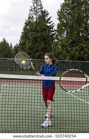 Young girl taking volley against opponent at the net with green trees in background - stock photo