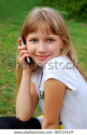 young girl talking by mobile phone sitting outdoor - stock photo