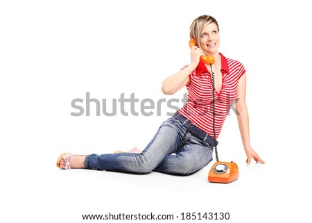 Young girl talking on a vintage phone isolated on white background - stock photo