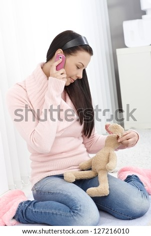 Young girl talking on mobile phone, holding soft toy bunny in hand.