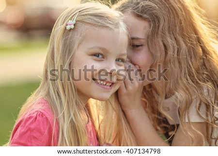 Young girl talking on the ear friend