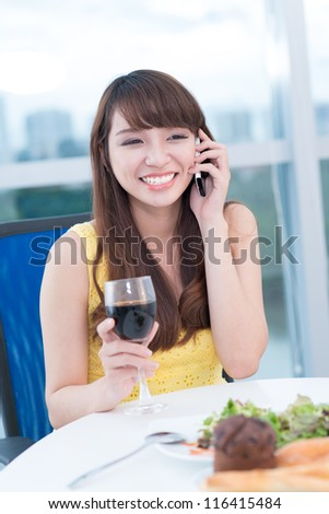 Young girl talking on the phone at restaurant and laughing