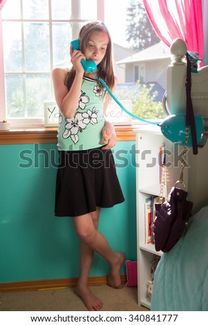 Young girl talking on the phone in her room