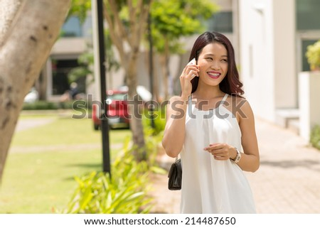 Young girl talking on the phone while walking along the street - stock photo