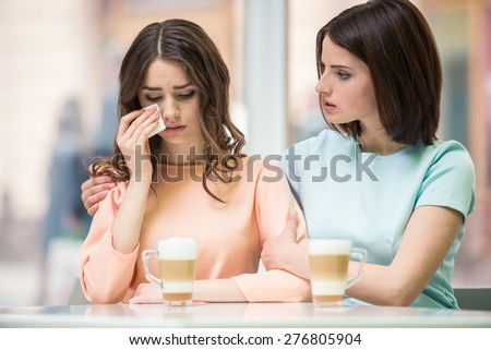 Young girl talking with her upset friend and holding her shoulders in cafe. - stock photo