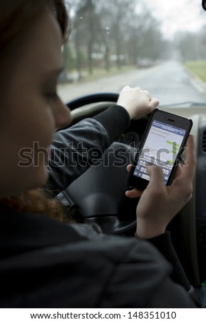 Young girl texting and driving, vertical - stock photo