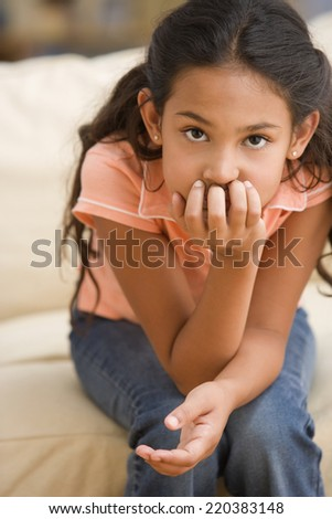 Young girl thinking while resting her chin in her hand - stock photo