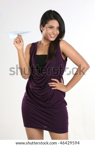 Young girl throwing blue paper plane over white - stock photo