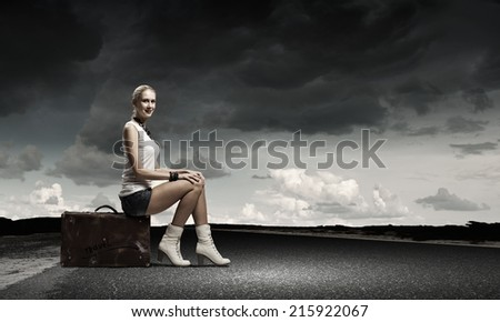 Young girl traveler in shorts sitting on suitcase
