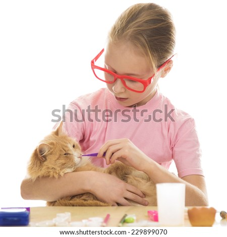 Young girl treats her kitten on a white background. - stock photo