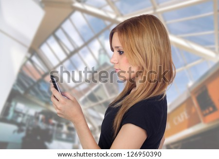 Young girl typing a message on mobile in a mall