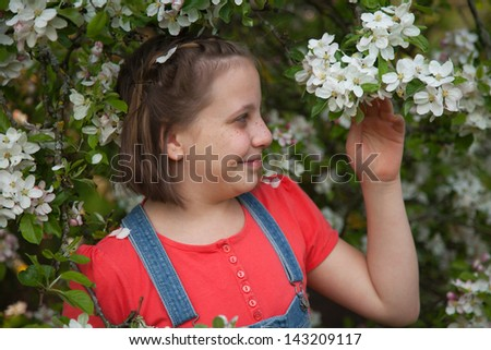 Young girl under a blooming apple tree in spring