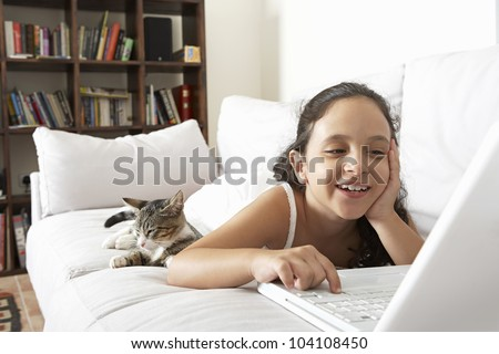 Young girl using a laptop computer at home while laying down on a white sofa with her cat. - stock photo