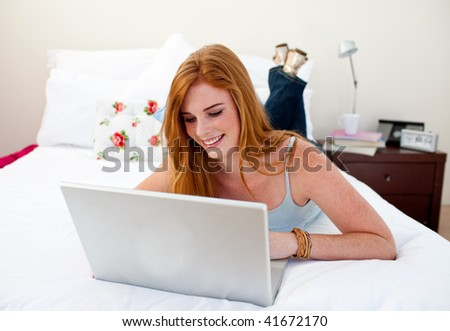 Young girl using a laptop in her bedroom - stock photo