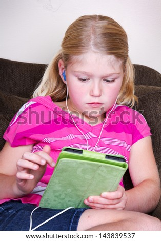 Young girl using a tablet with headphones sitting on couch