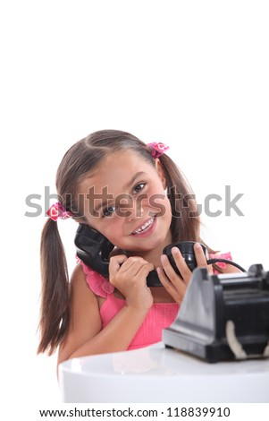 Young girl using an old fashioned black telephone - stock photo