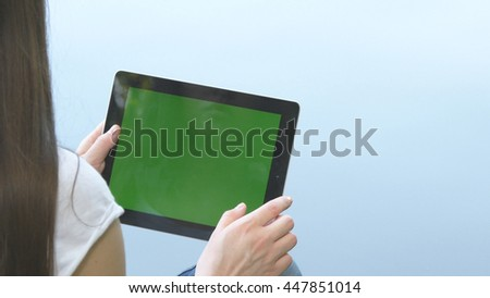 Young girl using digital tablet pc with green screen sitting on a wooden jetty by the lake. Rear view.