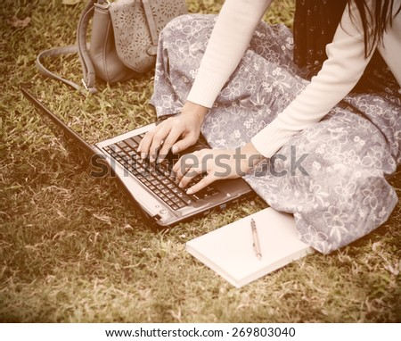 Young girl using laptop in park - Soft focus - stock photo